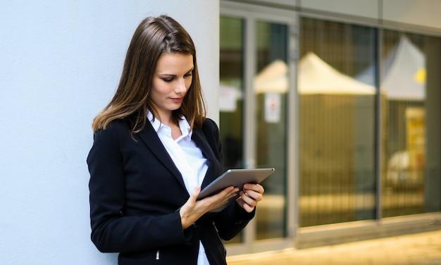 Donna di affari sorridente che per mezzo di una compressa digitale all'aperto