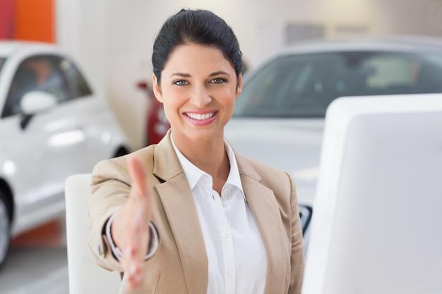 Donna di affari sorridente che raggiunge per l'handshake