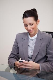 Donna di affari sorridente che si siede dietro lo scrittorio che scrive un textmessage