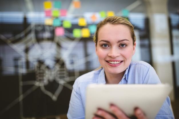 Donna di affari sorridente che tiene compressa digitale