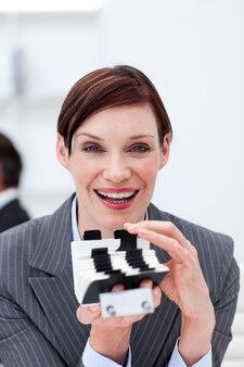 Donna di affari sorridente che tiene un titolare di carta