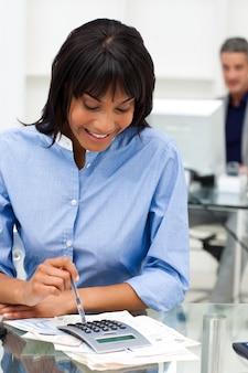 Donna di affari sorridente che usando un calcolatore