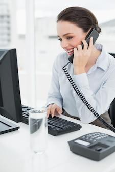 Donna di affari sorridente che utilizza telefono e computer della linea terrestre in ufficio
