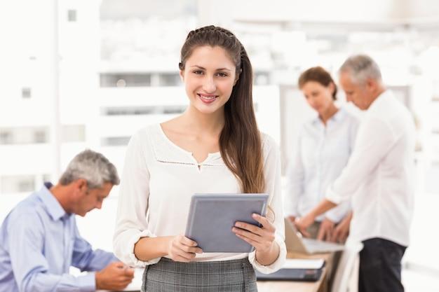 Donna di affari sorridente con il ridurre in pani in una riunione