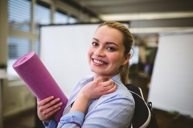Donna di affari sorridente con la borsa e la stuoia di esercizio