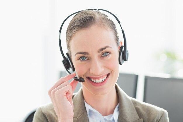 Donna di affari sorridente con la cuffia avricolare che esamina macchina fotografica