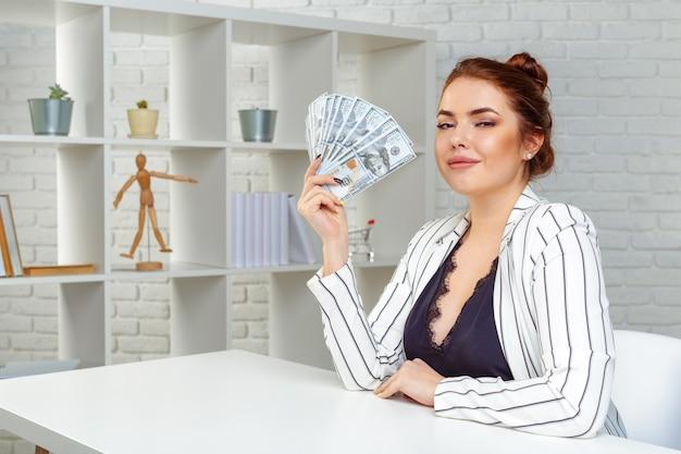 Donna di affari sorridente con le banconote del dollaro