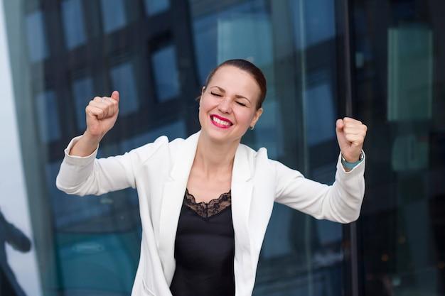 Donna di affari sorridente emozionante che celebra l'ufficio all'aperto di successo di affari. sì! femmina felice che trionfa con le mani sollevate