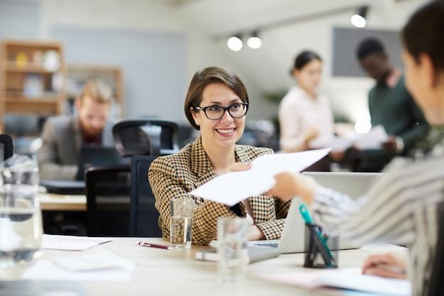 Donna di affari sorridente giving documents al collega