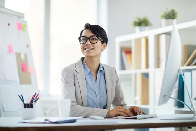 Donna di affari sorridente sul posto di lavoro