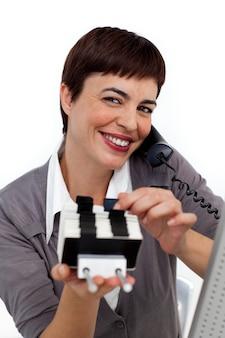Donna di affari sorridente sul telefono che consulta un titolare del biglietto da visita