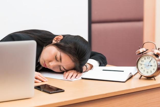 Donna di affari sovraccaricata e stanca che dorme sopra una scrivania sul lavoro nel suo ufficio.