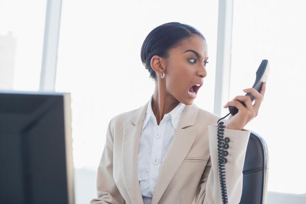 Donna di affari splendida furiosa che grida sul telefono