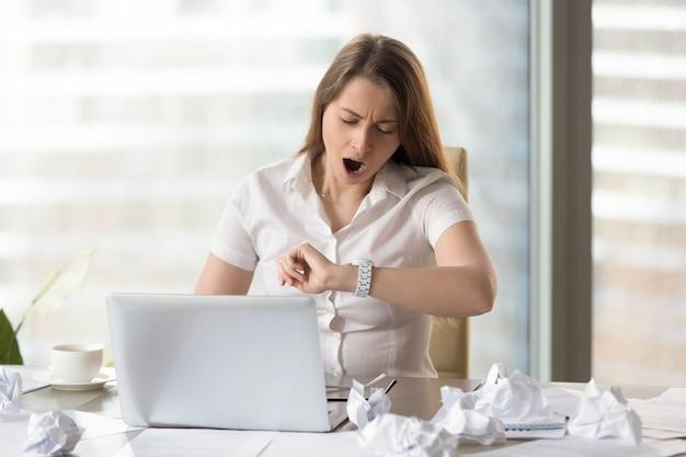 Donna di affari stanca che aspetta conclusione del giorno lavorativo