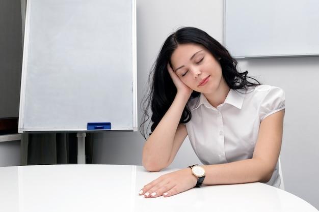 Donna di affari stanca che si siede nel luogo di lavoro