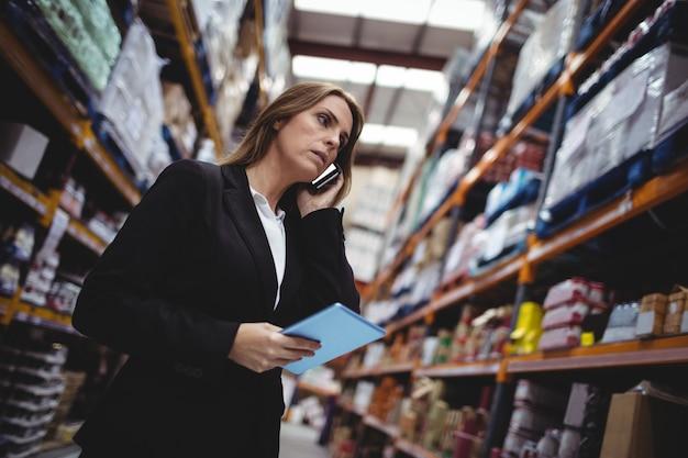 Donna di affari su una telefonata in magazzino