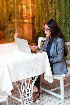Donna di affari sveglia e affascinante con i vetri che lavora al computer portatile dal ristorante o dal caffè