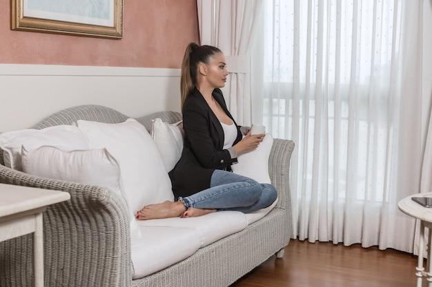 Donna di affari vaga con la bevanda calda che si siede sul sofà