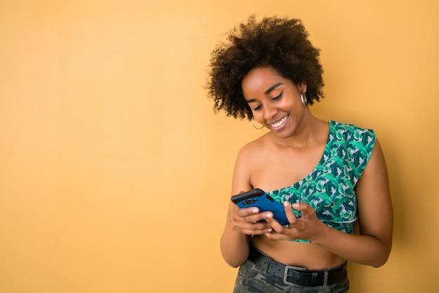 Donna di afro che per mezzo del suo telefono cellulare.