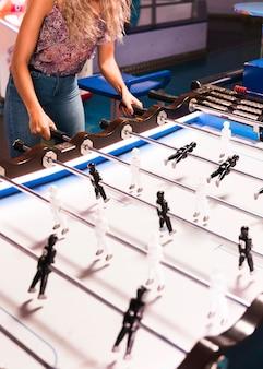 Donna di alta vista giocando a biliardino
