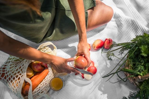 Donna di alto angolo che ha un picnic con spuntini sani