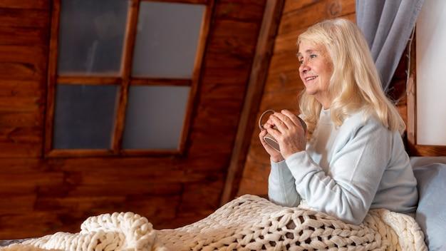 Donna di angolo basso a letto che beve tè