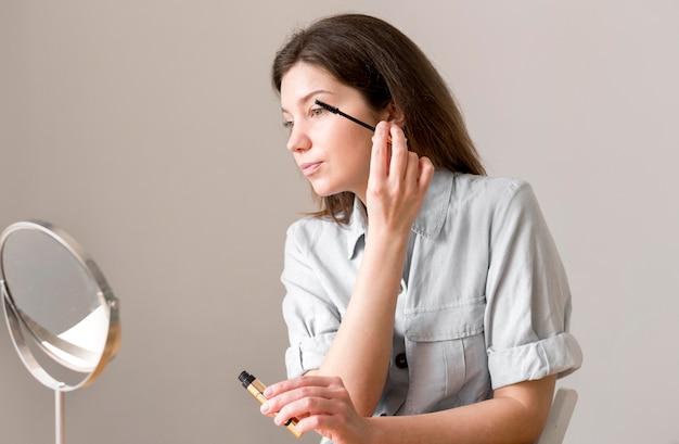 Donna di angolo basso che applica mascara