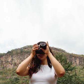 Donna di angolo basso che cattura le foto con copia-spazio