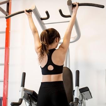 Donna di angolo basso che fa le esercitazioni per le braccia