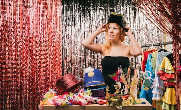Donna di angolo basso che prova sui cappelli
