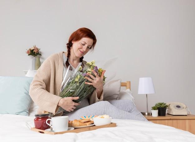 Donna di angolo basso con bouquet di fiori