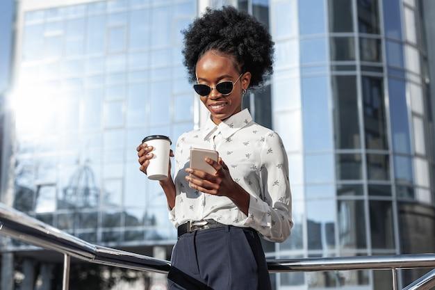 Donna di angolo basso con caffè che esamina cellulare