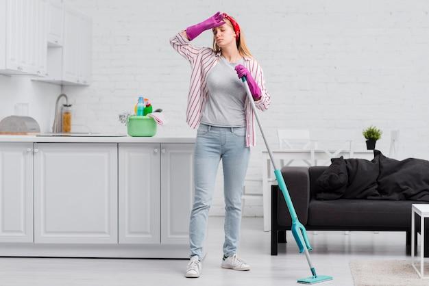 Donna di angolo basso stanca dalla pulizia