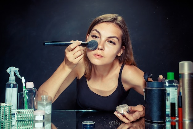 Donna di bellezza che applica trucco. bella ragazza guardarsi allo specchio e applicare cosmetici con un pennello grande.