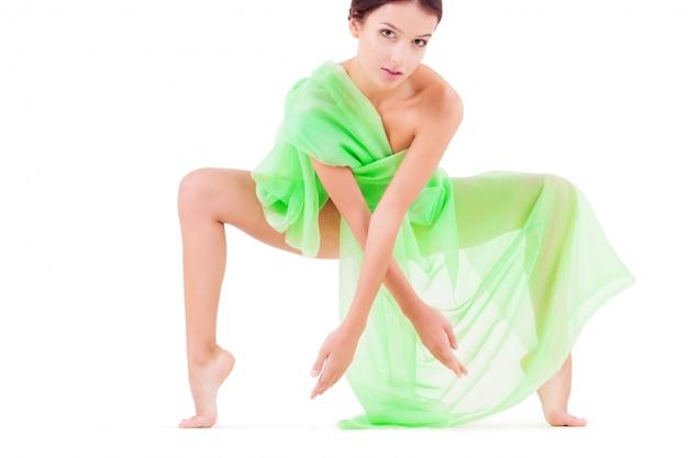 Donna di bellezza che posa con tessuto verde su bianco isolato