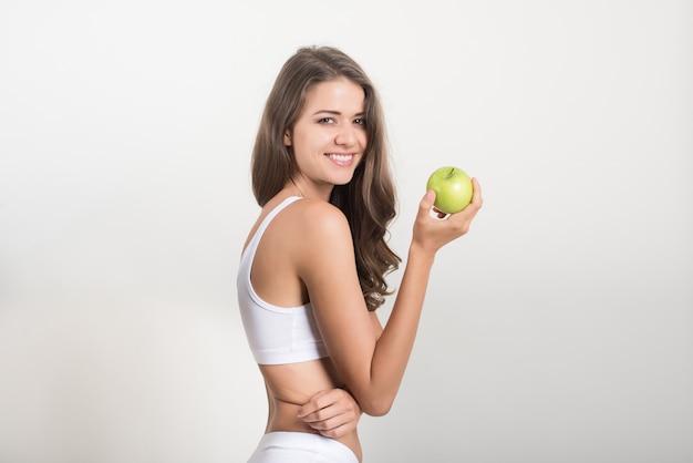 Donna di bellezza che tiene mela verde mentre isolato su bianco