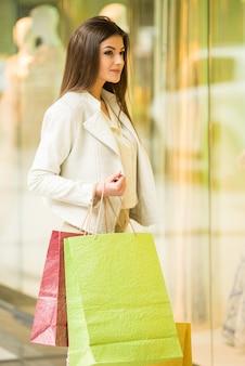 Donna di bellezza con i sacchetti della spesa nel centro commerciale.