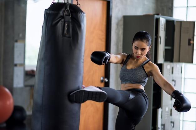Donna di boxe calciare enorme sacco da boxe in palestra