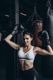 Donna di boxe in posa con il sacco da boxe. concetto di donna forte e indipendente