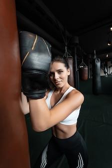 Donna di boxe in posa con il sacco da boxe, sul buio. concetto di donna forte e indipendente