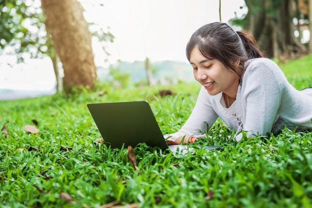 Donna di bueatiful con il computer portatile su erba verde in parco