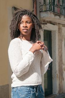 Donna di colore abbastanza giovane pensierosa che sta all'aperto