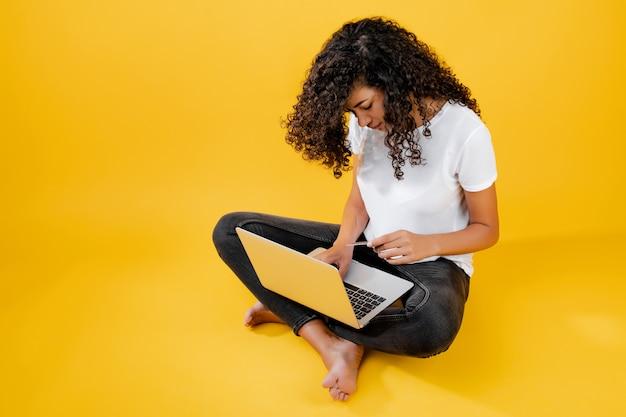 Donna di colore africana felice che si siede con il computer portatile e la carta di credito isolata sopra il giallo