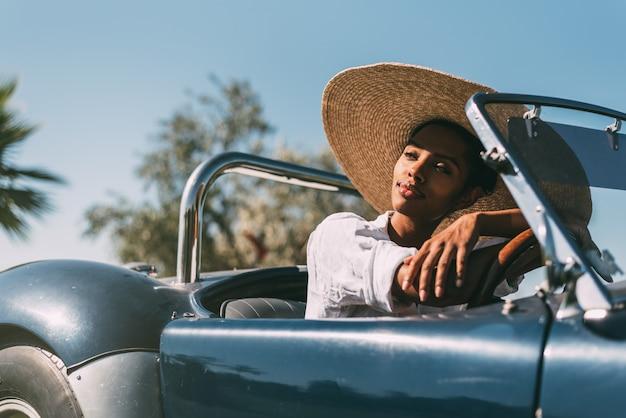 Donna di colore alla guida di un'auto convertibile vintage