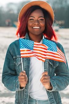 Donna di colore allegra che tiene le piccole bandiere degli stati uniti