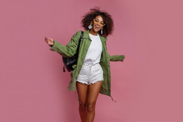 Donna di colore allegra divertendosi nello studio sopra fondo rosa. t-shirt bianca, giacca verde. elegante look primaverile.