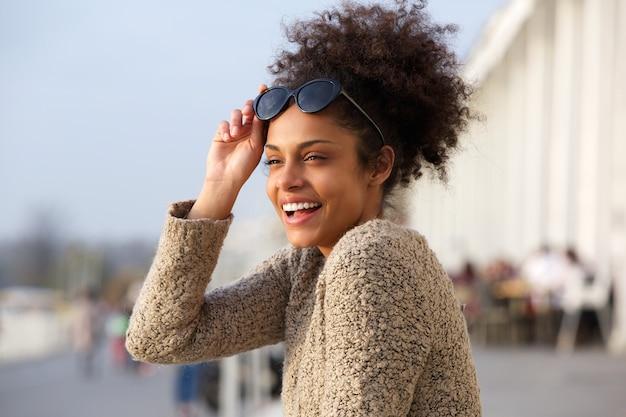 Donna di colore attraente che sorride all'aperto