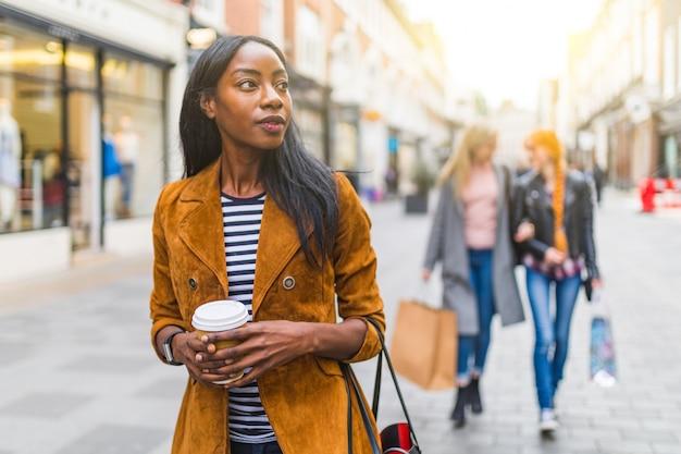 Donna di colore che cammina in città, tema dello shopping