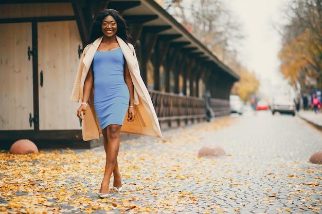 Donna di colore che cammina in una città di autunno