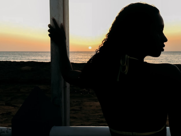 Donna di colore che osserva via il tramonto sulla spiaggia
